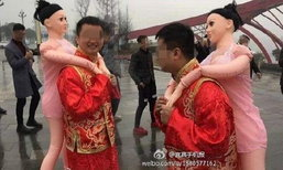 ดราม่าเบาๆ! หนุ่มใส่ชุดแต่งงานแบบจีนแบกตุ๊กตายางเดินเตร่ทั่วถนน