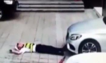 รปภ.นอนขวางเก๋งไม่ให้เข้าไปจอด ถูกสาวขับรถทับทั้งตัว