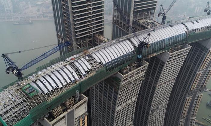 """อลังการอีกแล้ว จีนประกอบร่าง """"เรือนกระจก"""" ใหญ่สุดในโลก เชื่อมตึกสูง 250 เมตร"""