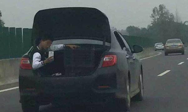 ชิลล์ไปไหน..? หนุ่มจีนเซลฟี่-เล่นมือถืออยู่กระโปรงท้ายรถ